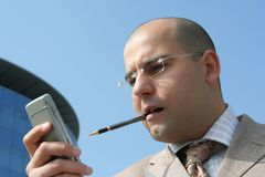 Businessman an cell phone. Business man holding cell phone up the business building Stock Images