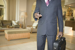 Businessman With Cell Phone And Briefcase In Hotel Lobby Royalty Free Stock Images