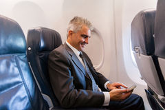Businessman cell phone. Happy middle aged businessman using cell phone on airplane Stock Photos