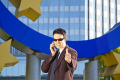 Businessman with cell phone posing thumbs up Stock Image
