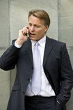 Businessman on cellphone. An angry forties businessman wearing a smart suit is arguing with somebody on his cellphone Stock Photos