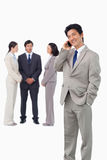 Businessman with cellphone and colleagues behind him Stock Image