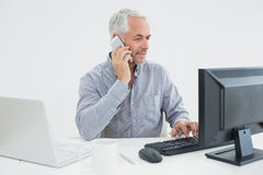 Businessman with cellphone, laptop and computer at desk Stock Photography