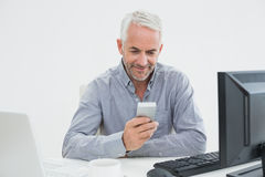 Businessman with cellphone, laptop and computer at desk Stock Image