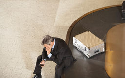 Businessman With Cellphone By Luggage On Carousel In Airport Royalty Free Stock Photo