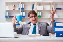 The businessman chained with handcuffs to his coffee. Businessman chained with handcuffs to his coffee Stock Photography