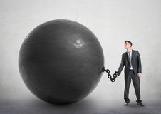 Businessman chained to a large ball royalty free stock image