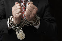 Businessman in chains. Close up of businessmans hands tied in heavy chains with padlock royalty free stock image