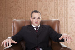 Businessman on a chair, Stock Images