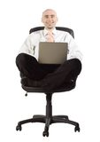 Businessman in chair with laptop computer. Isolated businessman in casual position in a black chair smiles while working on laptop computer royalty free stock image