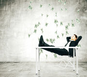 Businessman on a chair in loft room with money falling from the Stock Photo