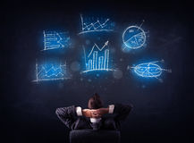 Businessman in chair looking at charts Royalty Free Stock Photos