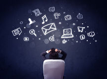 Businessman in chair with multimedia icons over his head Royalty Free Stock Image