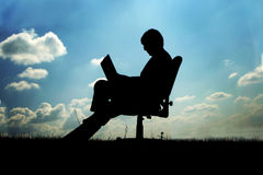 Businessman in chair outside. Silhouette of a businessman with laptop sitting in an office chair outdoors against a blue cloudy sky Stock Photos