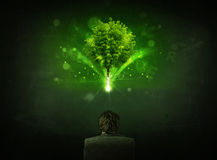 Businessman in chair sitting in front of a glowing tree. Young businessman sitting in office chair with a glowing tree and letters above his head Stock Photos