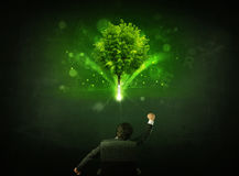 Businessman in chair sitting in front of a glowing tree. Young businessman sitting in office chair with a glowing tree and letters above his head Stock Photo