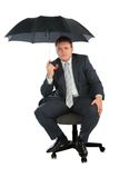 Businessman on chair with umbrella stock images