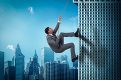 The businessman in challenge concept climbing skyscraper Stock Images