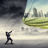 Businessman change the friendly environment. Businessman change the environment by pulling an air pollution banner to a banner of green city Royalty Free Stock Photo