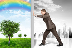 Businessman changing nature landscape on grey city Stock Photography