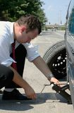 Businessman changing a tire. Businessman changing a flat tire on the road Stock Images