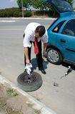 Businessman changing a tire. Businessman changing a flat tire on the road Stock Photos