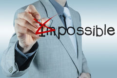 Businessman changing the word impossible into possible Royalty Free Stock Photography