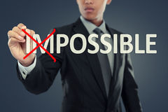 Businessman changing word impossible into possible. On virtual background stock image