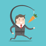 Businessman chasing carrot. Enthusiastic businessman chasing motivational carrot hanging in front of him. Goal, motivation, career, reward and performance Royalty Free Stock Photography