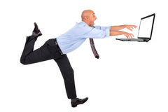 Businessman chasing laptop Royalty Free Stock Photography