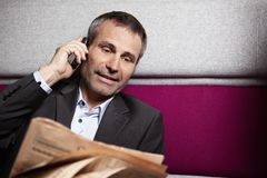 Businessman chatting on phone with newspaper. Stock Photos