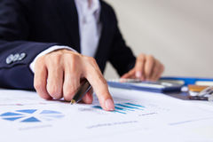 Businessman check seriously analyzes a finance report investor colleagues discussing new plan financial graph data. Finance manage. Rs task. Concept business and Royalty Free Stock Photo