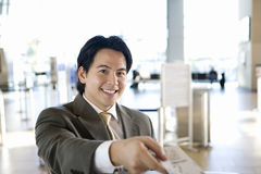 Businessman checking in at airport, receiving boarding pass from check-in attendant, smiling, portrait, view from behind check-in  Royalty Free Stock Photo