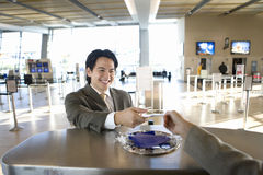 Businessman checking in at airport, receiving boarding pass from check-in attendant, view from behind check-in desk Royalty Free Stock Image