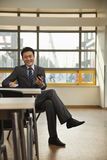 Businessman checking cell phone in company cafeteria Royalty Free Stock Photography