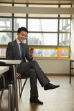 Businessman checking cell phone in company cafeteria Stock Image