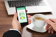 Businessman checking credit score on cellphone. Close-up Of A Businessman Checking Credit Score Online On Cellphone While Having Coffee Royalty Free Stock Photo