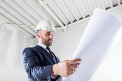 Businessman checking documents at the construction site. Stock Photo