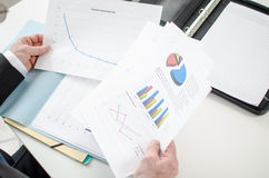 Businessman checking a file with financial graphs Stock Photography
