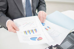 Businessman checking a file with financial graphs Stock Photos