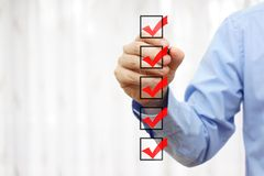 Businessman checking final mark on checklist stock images