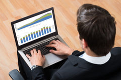 Businessman Checking Financial Report On Laptop stock photo