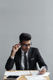 Businessman checking his phone and  papers on his desk. Businessman checking his phone and Royalty Free Stock Photo