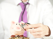 Businessman checking piggy bank Stock Images