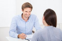 Businessman checking resume of female candidate during meeting. Mid adult businessman checking resume of female candidate during meeting in office stock photography