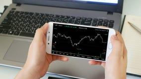 Businessman checking stock market dataมStock Market Application for Mobile, Analyzing Data Stock Market on Mobile Young royalty free stock image