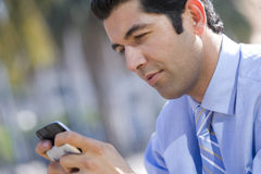 Businessman checking text messages on cell phone Stock Images