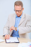 Businessman checking the time while doing Royalty Free Stock Photo