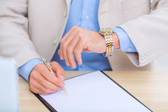 Businessman checking the time while doing Stock Photo