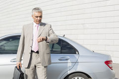Businessman checking the time in front of car outdoors Stock Photo